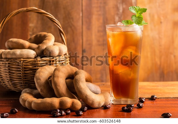 Delicious sweet drink tamarind juice and ice with mint leaves on rustic wooden table. Selective focus and toned image. Copy space.