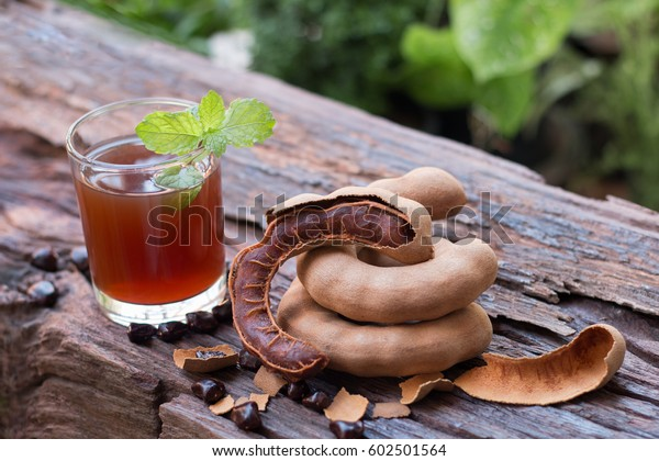 Delicious sweet drink tamarind, ripe tamarinds and seeds with mint leaves on rustic wooden table. Selective focus and toned image. Copy space.