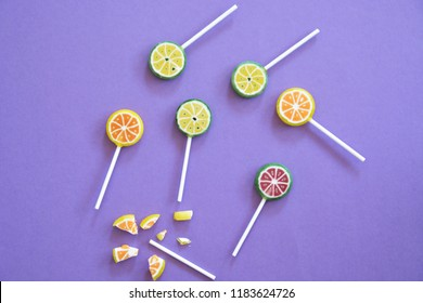 Delicious sweet lollipops with the appearance of fruits like lime and lemon or watermelon on a colored background