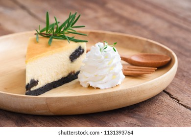Delicious and sweet original plain New York cheesecake on wooden plate served with whipped cream on wood table with copy space in side view. Homemade bakery for cafe and restaurant or birthday cake.