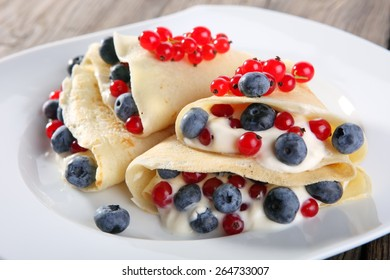 Delicious sweet pancakes on a plate with fresh fruits and addons.