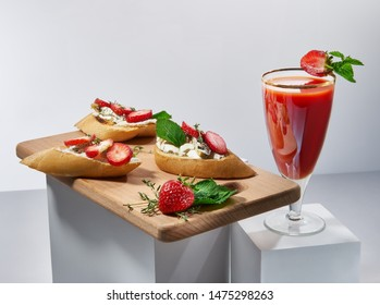 Delicious sweet red cocktail and canapes with butter and yummy strawberries. Nice beverage and snacks on white cubes. Gourmet and sophisticated drinks and appetizers concept