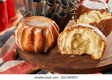 Delicious Sweet Rum Baba cake with powdered sugar glaze on a wood cutting board. Traditional italian fluffy fancy bread with cup of tea. Low key