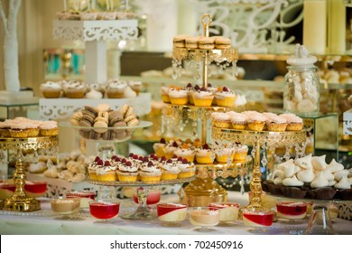 Delicious sweets on candy buffet. Wedding candy bar decoration setup with delicious cakes and sweets. Candy bar.