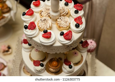 Delicious sweets/Cookies support with several levels holding a variety of delicious desserts seasoned with berries cream and frosting.