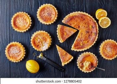 delicious Swiss Easter Rice Tarts sprinkled with powdered sugar and lemon zest, gateau de Paques, Osterfladen in tart shells, on a black wooden table with lemon, horizontal view from above, flat lay
