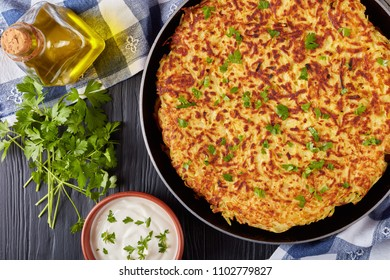 delicious swiss rosti or potato pancake sprinkled with finely chopped parsley in a skillet on a black wooden table with sour cream in a bowl and a bottle of olive oil, close-up