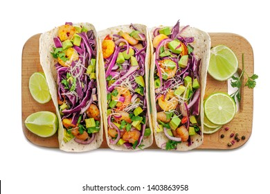 Delicious tacos with shrimps, avocado, onion and lime on a wooden board. Classic Tex-Mex cuisine meal. Top view shot, directly above studio shot on white background.