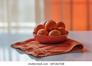 Delicious tangerines on a plate and orange towel on a table by the window