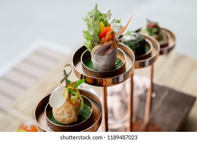 Delicious Taps with an Asian twist on vintage copper chandelier stand at the hotel restaurant. Attractive Hotel's guest amenity setup and decoration.