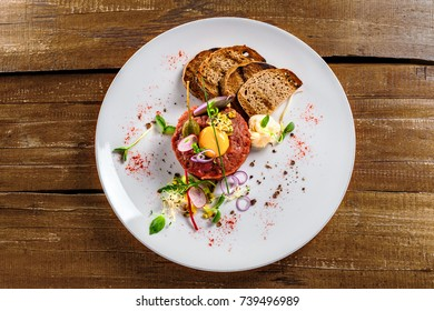 Delicious tartare with toasted bread and salad on a plate. Healthy lunch meal made of raw meat. Classical French cuisine.  Top view.