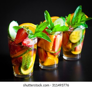Delicious and tasty alcohol cocktail Pimms. Beautiful black background. Bar and Pub concept. Fruit salad with strawberries.
