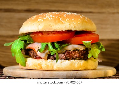 Delicious tasty burger with beef, tomatoes, salad and sauce on board on wooden  background, close-up