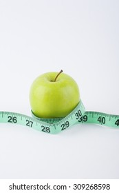 Delicious and tasty green apple with green measuring tape - diet, fitness, lifestyle, healthy and vegetarian concept