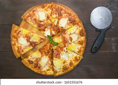 Delicious tasty hot hawaiian exotic sliced pizza with sweet pineapple slices, chicken meat, sauce and cheese. Pizza cutter knife slicer. Top view on dark wooden brown background. National italian food