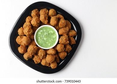 Delicious tasty moong vada and moong pakoda, yummy delicious moong or mung dal bhajiya or bajji or moong Cade or pakora with red sauce and green chutney