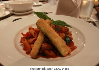 Delicious and tasty penne in a bolognese sauce serve on the white plate compliment with fried egg plant and basil leaf