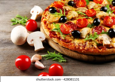 Delicious tasty pizza with ingredients on wooden table