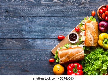 Delicious and Tasty sandwiches with turkey, ham, cheese, tomatoes and salad over a wooden table full of fresh vegetables.