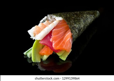 Delicious Temaki Sushi with salmon, tuna, shrimp, avocado and cucumber on black background. Traditional Japanese cuisine