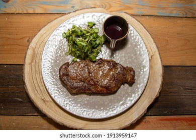 A delicious tender tenderloin steak on a plate with a a pot of red wine sauce and garnish on a wooden kitchen table