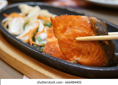 delicious Teppanyaki Salmon food with chopsticks and vegetable in the iron pan and wood chopping board on the table at Japanese restaurant for lunch or dinner