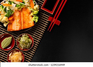 delicious Teppanyaki Salmon grill food with vegetable in the iron pan. Top view