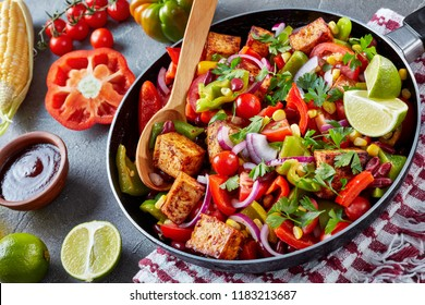 Delicious texan dish: chopped bell pepper, tomato, onion, parsley, tofu, corn, black bean, lime and barbecue sauce on a concrete background, close up, horizontal
