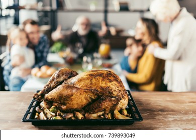 delicious thanksgiving turkey on table with blurred family on background
