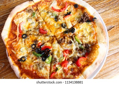 Delicious thin crust Italian pizza with red and green chili and mozzarella cheese that served on the wooden table for lunch