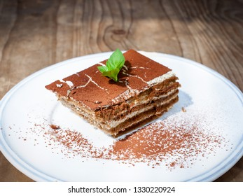 Delicious Tiramisu cake on a white plate.with a copy space.