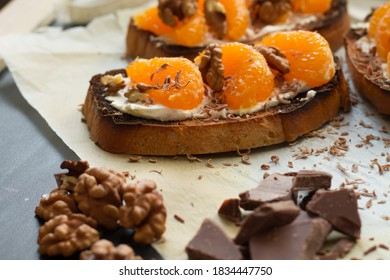 Delicious toast with sweet tangerine and cream cheese on black wooden background. Copy space.