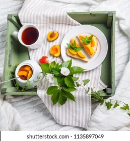 Delicious toasts bread with homemade apricot jam and cup of tea on tray, on background of the flowers of convolvulus