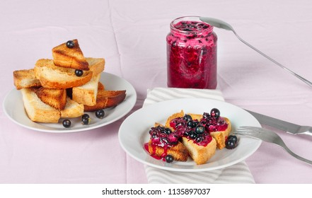 Delicious toasts bread with homemade currant jam with fork and knife on bright crimson tablecloth