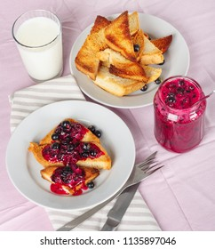 Delicious toasts bread with homemade currant jam with milk on bright crimson tablecloth
