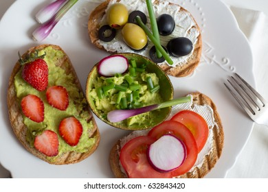 Delicious toasts with guacamole dip, avocado, strawberries, cheese, tomatoes and olives on white rustic plate. Set of appetizers.