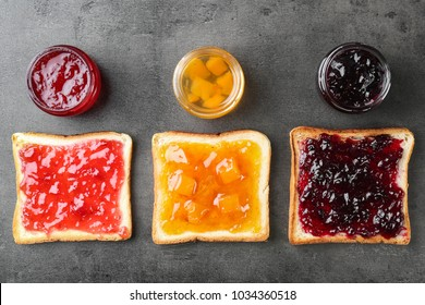Delicious toasts with various sweet jams on grey background