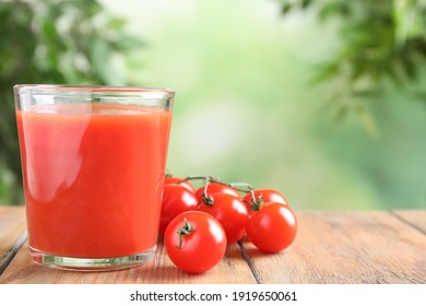 Delicious tomato juice and vegetables on wooden table. Space for text