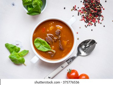 Delicious tomato soup with meat on a white rustic wooden table with fresh cherry tomatoes, basil leaves and dry pepper. Ingredients for soup. Top view