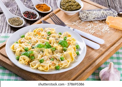 Delicious tortellini with green peas, fried Pine nuts, decorated with basil leaves on a white dish with spice, sauce pesto and parmesan cheese on an old rustic table, italian style. close-up