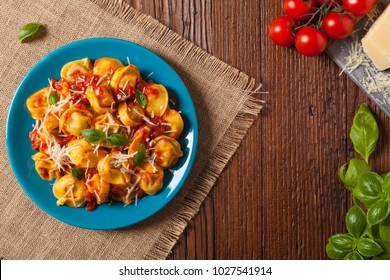 Delicious tortellini with meat in tomato sauce, sprinkled with parmesan cheese and basil. Top view.