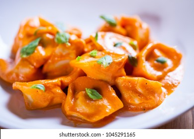 Delicious tortellini pasta in red tomato sauce with basil and parmesan cheese. Tortellini pasta on white plare. Fine dish. Italian food Home made fresh tortelini