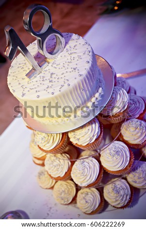 Delicious Tower Birthday Cake With Cupcakes In The Base And A White Creamy On Top