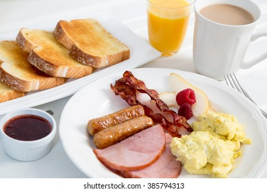 A delicious traditional American breakfast of bacon, sausage, ham and scrambled eggs with all the trimmings on a nice bright white tablecloth