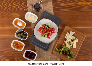 Delicious Traditional Diet Turkish breakfast on a big wood table. Turks usually prefer a rich breakfast. Typical consists of cheese, butter, olives, eggs, tomatoes, cucumbers, jam, honey, and kaymak.