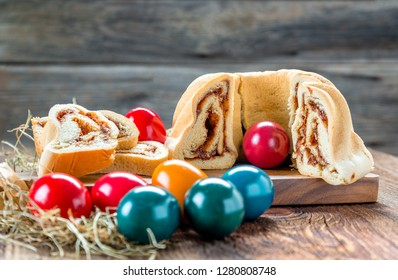 Delicious traditional Easter snack with cakes and eggs served on a rustic wooden board