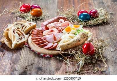 Delicious traditional Easter snack with ham, sausages, eggs and various side dishes served on a rustic wooden board