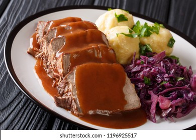 Delicious traditional German dinner Sauerbraten - slowly stewed marinated beef with gravy with potato dumplings and red cabbage close-up on a plate. horizontal