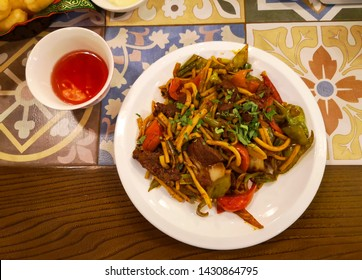 Delicious traditional homemade pasta with lamb and fresh vegetables serviced with fruit tea, Bishkek, Krygyzstan