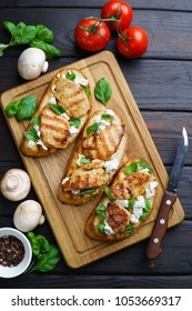 Delicious traditional Italian antipasti bruschetta with grilled chicken, ricotta and basil flat lay on wooden board, vertical image